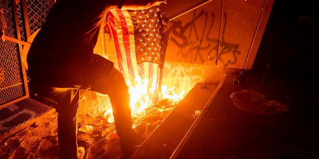 A Black Lives Matter protester burns an American flag outside the Mark O. Hatfield United States Courthouse on Monday in Portland, Ore. (AP Photo/Noah Berger)
