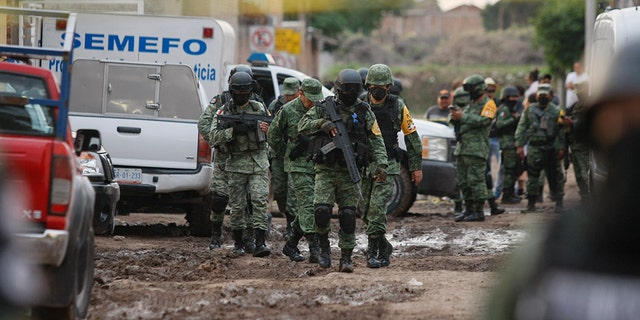 Members of the national guard walk near an unregistered drug rehabilitation center after a shooting in Irapuato, Mexico, Wednesday, July 1, 2020. (Associated Press)