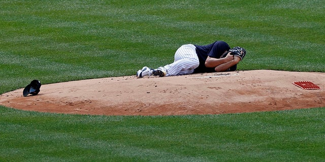 New York Yankees pitcher Masahiro Tanaka lies on the field after being hit by a ball off the bat of Yankees Giancarlo Stanton during a baseball a workout at Yankee Stadium in New York, Saturday, July 4, 2020. (Associated Press)