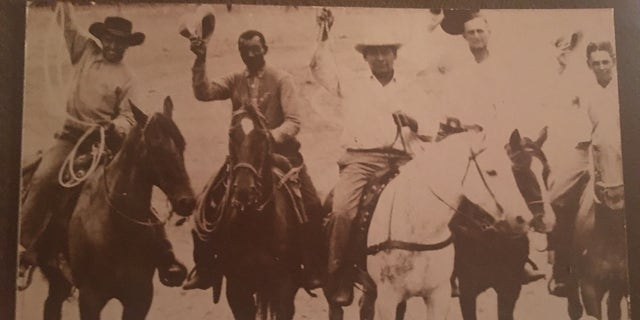 Bill Pickett (second from left) can be seen on horseback. He was one of the first great rodeo cowboys and the first African-American inducted into the National Rodeo Hall of Fame.