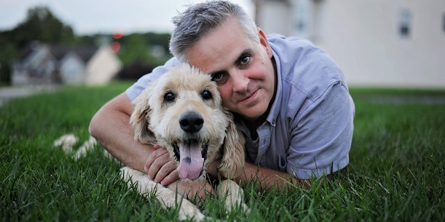 Jason Wright with Goldendoodle Pilgrim before trip to veton his final morning