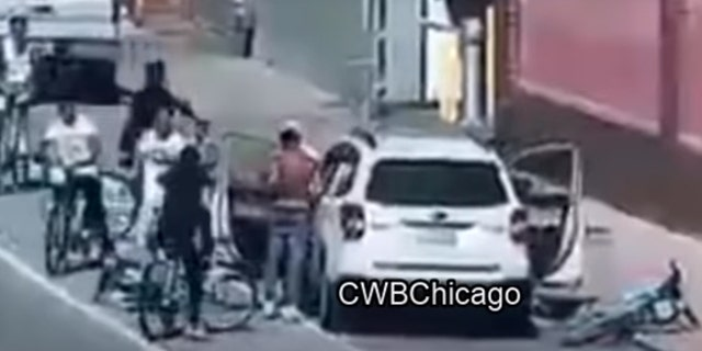 The alleged assailants yanked the victim out of his white SUV, tossed some of his belongings onto the street and left him standing on the side of the road as they sped off. (Courtesy:CWBChicago)