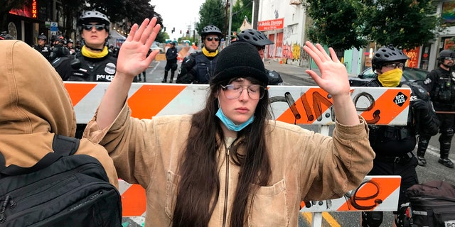 A protester stands with her hand up in front of a road blocked by Seattle police in the Capitol Hill Organized Protest zone early Wednesday. Police in Seattle have torn down demonstrators' tents in the city's so-called occupied protest zone after the mayor ordered it cleared. (AP Photo/Aron Ranen)