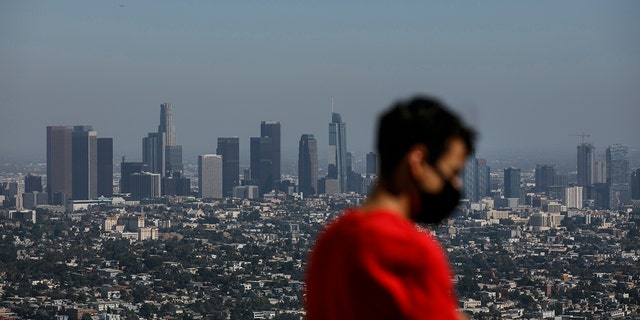 """Izzy Galvan, 20, wears a face mask while visiting the Griffith Observatory overlooking downtown Los Angeles, Wednesday, July 15, 2020, in Los Angeles. Coronavirus cases have surged to record levels in the Los Angeles area, putting the nation's largest county in """"an alarming and dangerous phase"""" that if not reversed could overwhelm intensive care units and usher in more sweeping closures, health officials said Wednesday. (AP Photo/Jae C. Hong)"""