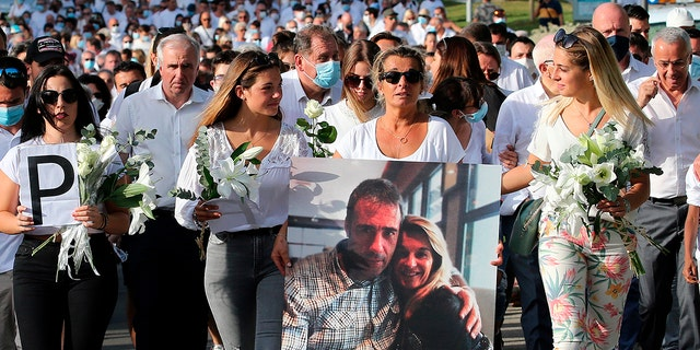 Veronique Monguillot, wife of Philippe Monguillot, a bus driver who was attacked in Bayonne on Sunday night, holding a photo of her with her husband, during a protest march in Bayonne, southwestern France. (AP Photo/Bob Edme)