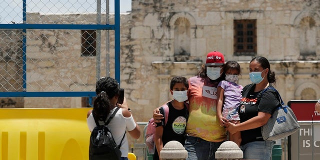 Visitors wearing masks to protect against the spread of COVID-19 pose for photos at the Alamo, which remains closed, in San Antonio last month. Cases of COVID-19 have spiked in Texas to over 200,000, according to government figures. (AP Photo/Eric Gay)