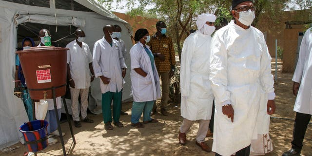 In this photo taken Thursday, May 21, 2020, a delegation led by Mali's Minister of Health Michel Sidibe, right, visits the isolation tent for patients with the coronavirus in Timbuktu, Mali. COVID-19 has made its way to Timbuktu, a town whose name has long been synonymous around the world with remoteness. (AP Photo/Baba Ahmed)