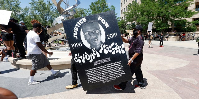 In this June 27, 2020, file photo, demonstrators carry a giant placard during a rally and march over the death of 23-year-old Elijah McClain outside the police department in Aurora, Colo. Multiple suburban Denver police officers have been placed on paid administrative leave amid an investigation into photos of them related to the case of a Black man who died last summer after he was stopped and restrained, police said Monday, June 29, 2020. (AP Photo/David Zalubowski, File)