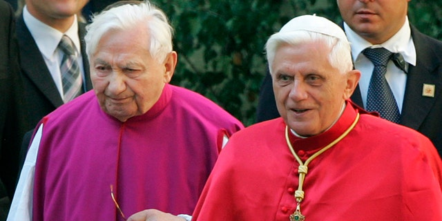 In this Sept. 13, 2006 file picture Pope Benedict XVI, right, walks with his brother priest Georg Ratzinger in Regensburg, southern Germany. The Rev. Georg Ratzinger, the older brother of Emeritus Pope Benedict XVI, who earned renown in his own right as a director of an acclaimed German boys' choir, has died at age 96. The Regensburg diocese in Bavaria, where Ratzinger lived, said in a statement on his website that he died on Tuesday, June 30, 2020. (AP Photo/Diether Endlicher)