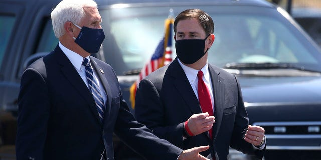 Vice President Mike Pence, left, walks with Arizona Gov. Doug Ducey, right, after their meeting to discuss the surge in coronavirus cases in Arizona Wednesday, July 1, 2020, in Phoenix. (AP Photo/Ross D. Franklin)