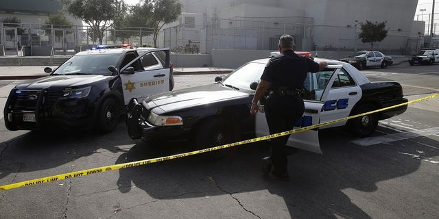 Los Angeles Sheriffs officers and Los Angeles Unified School District police officers guard the campus of Esteban Torres High School in unincorporated East Los Angeles. (AP Photo/Damian Dovarganes, File)