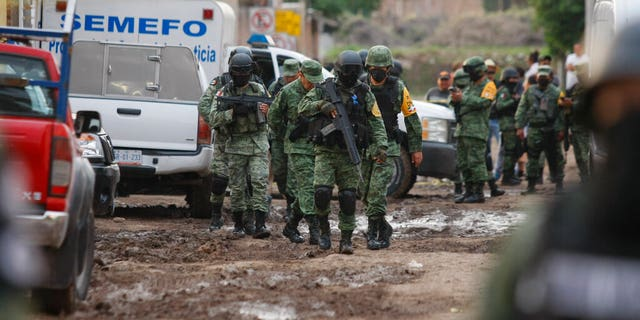 Members of the national guard walk near an unregistered drug rehabilitation center after a shooting in Irapuato, Mexico, Wednesday, July 1, 2020.