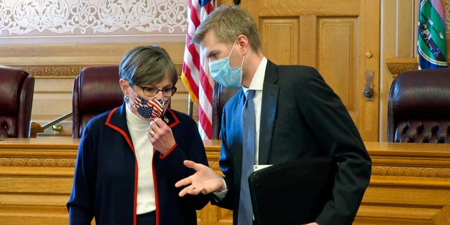 Kansas Gov. Laura Kelly, left, confers with Clay Britton, her chief attorney, before a meeting with legislative leaders.