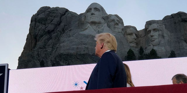 President Donald Trump watches as planes perform fly-overs of the Mount Rushmore National Monument Friday, July 3, 2020, in Keystone, S.D. (Associated Press)
