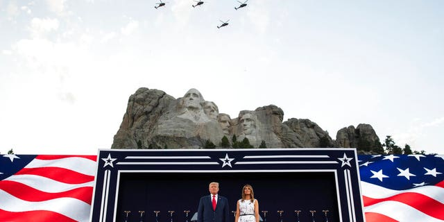 President Donald Trump, accompanied by first lady Melania Trump, stand during a flyover at Mount Rushmore National Memorial, Friday, July 3, 2020, near Keystone, S.D.