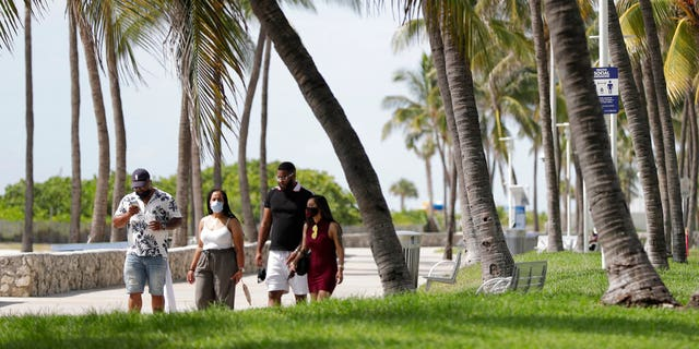 A group of people, wearing face masks to prevent the spread of the coronavirus, walk along a beach path on Miami Beach, Florida's famed South Beach, July 4, 2020.