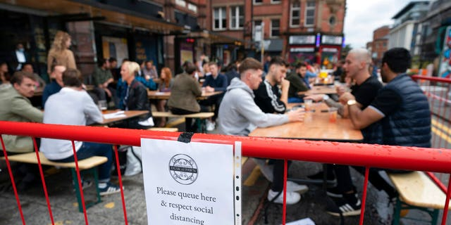 Members of the public are seen at a bar in Manchester's Northern Quarter, England, Saturday July 4, 2020. England is embarking on perhaps its biggest lockdown easing yet as pubs and restaurants have the right to reopen for the first time in more than three months Saturday. (AP Photo/Jon Super)