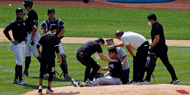 New York Yankees pitcher Masahiro Tanaka is tended to by team medical personnel after being hit by a ball off the bat of Yankees Giancarlo Stanton during a baseball a workout at Yankee Stadium in New York, Saturday, July 4, 2020. (Associated Press)