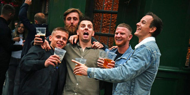 Men pose for a photo, outside a pub as it reopened, in Borough Market, as coronavirus lockdown restrictions eased across England, in London, Saturday, July 4, 2020. (Victoria Jones/PA via AP)