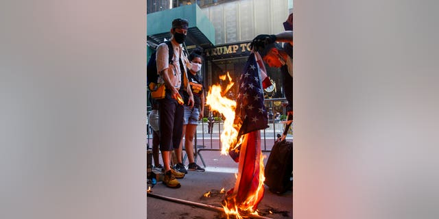 Protesters burn U.S. flags during a protest in front of Trump Tower on Fifth Avenue, Saturday, July 4, 2020, in New York.