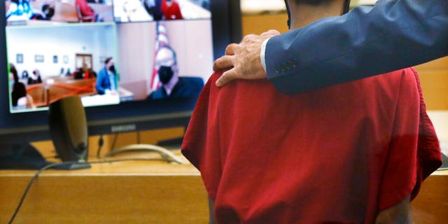 Attorney John Henry Browne puts his arm over the shoulders of Dawit Kelete as Kelete makes a court appearance before Judge Mark Chow, on video, Monday, July 6, 2020, in Seattle. Kelete is accused of driving a car onto a closed Seattle freeway and hitting two protesters, killing one, over the weekend. Seattle has been the site of prolonged unrest over the death of George Floyd, a Black man who was in police custody in Minneapolis.