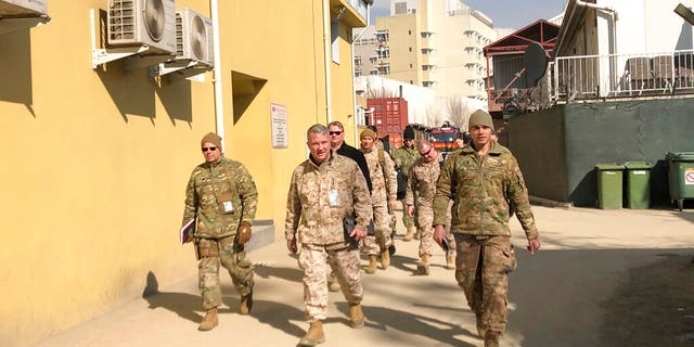In this Jan. 31, 2020, file photo, Marine Gen. Frank McKenzie, center, top U.S. commander for the Middle East, makes an unannounced visit in Kabul, Afghanistan. Six months after a deadly American airstrike in Baghdad enraged Iraqis and fueled demands to send all U.S. troops home, McKenzie is talking optimistically about keeping a smaller, but enduring military presence in Iraq. (AP Photos/Lolita Baldor, File)