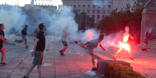 Protesters charge the building of the Serbian parliament in Belgrade, Serbia, Wednesday, July 8, 2020. (AP Photo/Marko Drobnjakovic)