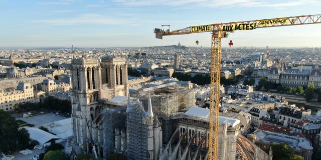 "In this handout photograph provided by Greenpeace, a banner hanging from a crane reads ""Climate. In action"", near Notre Dame Cathedral, in Paris, Thursday, July 9, 2020. Greenpeace activists hung banners from the huge construction crane atop Notre Dame Cathedral in Paris on Thursday accusing France and President Emmanuel Macron of not doing enough to fight climate change. (AP Photo/Greenpeace, HO)"
