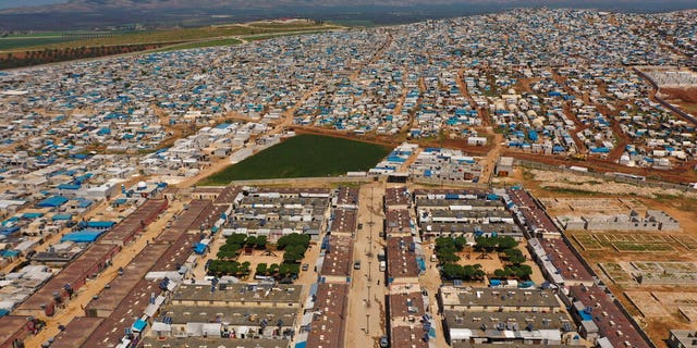 FILE - In this April 19, 2020 photo file photo, shows a large refugee camp on the Syrian side of the border with Turkey, near the town of Atma, in Idlib province, Syria. (AP Photo/Ghaith Alsayed, File)