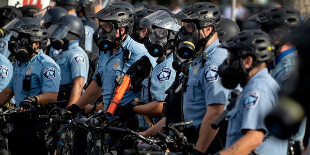 In this May 27, 2020, file photo, police gather en masse as protests continue at the Minneapolis 3rd Police Precinct in Minneapolis. The Minneapolis protests sparked others nationwide. (Carlos Gonzalez/Star Tribune via AP, File)