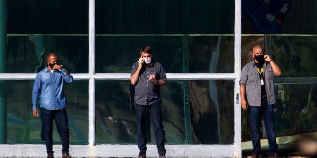 Brazil's President Jair Bolsonaro, center, talks on his phone while standing outside his official residence Alvorada Palace, in Brasilia, Brazil, Friday, July 10, 2020. (AP Photo/Eraldo Peres)