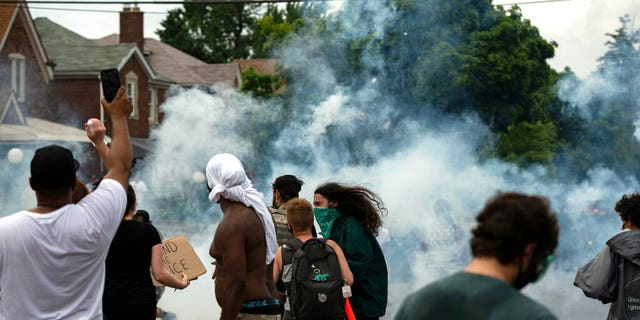 Protesters against police brutality clash with police during a march near where 20-year-old Hakeem Littleton was killed in a shootout with Detroit police earlier in the day, Friday July 10, 2020, in Detroit. (Nicole Hester/Ann Arbor News via AP)