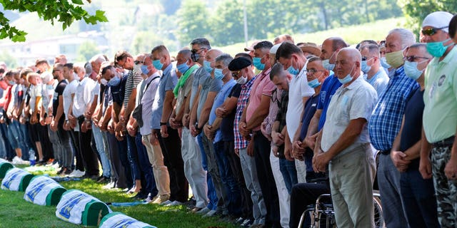 Bosnian pray by the coffins of the victims during the burrial in Potocari, near Srebrenica, Bosnia, Saturday, July 11, 2020.