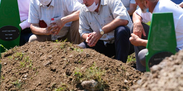 Bosnians pray during the burial of nine war victims in Potocari near Srebrenica Bosnia Saturday