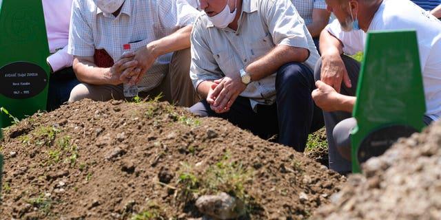 Bosnians pray during the burial of nine war victims in Potocari, near Srebrenica, Bosnia, Saturday, July 11, 2020.