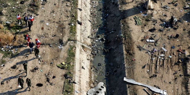 FILE: Rescue workers search the scene where a Ukrainian plane crashed in Shahedshahr, southwest of Tehran, Iran.