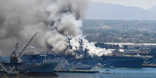 Smoke rises from the USS Bonhomme Richard at Naval Base San Diego Sunday, July 12, 2020, in San Diego after an explosion and fire Sunday on board the ship at Naval Base San Diego.
