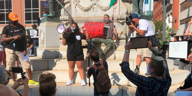 Activist Maegan Llerena addresses a crowd of protesters in Allentown, Pa. who gathered Monday, July 13, 2020, to demand accountability from police after video emerged of an officer placing his knee on a man's head and neck area outside a hospital. Police have launched an internal probe. (AP Photo/Michael Rubinkam)