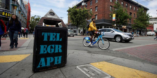 FILE - In this July 18, 2019, file photo, traffic and pedestrians cross Telegraph Avenue in Berkeley, Calif. The politically liberal city of Berkeley in Northern California is considering a proposal to shift traffic enforcement from armed police to unarmed city workers. (AP Photo/Jeff Chiu, File)