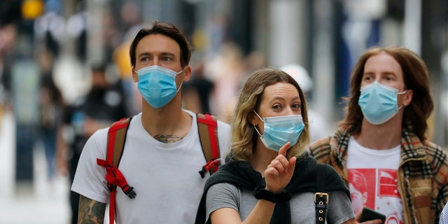Shoppers wearing protective face masks walk along Oxford Street in London, Tuesday, July 14, 2020. Britain's government is demanding people wear face coverings in shops as it has sought to clarify its message after weeks of prevarication amid the COVID-19 pandemic. (AP Photo/Frank Augstein)