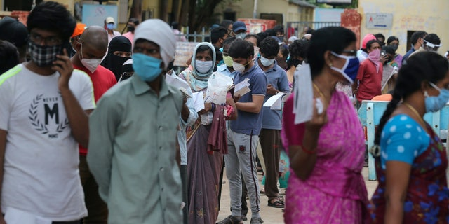 Indian people form a queue to get a nasal swab test for the coronavirus at Government Fever hospital in Hyderabad India Wednesday