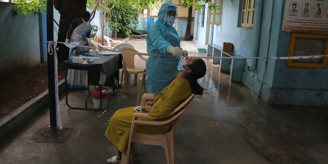 A woman gets a nasal swab taken to test for the coronavirus at Government urban primary health center in Hyderabad, India, Wednesday, July 15, 2020. India is the third worst-affected nation by the coronavirus pandemic. (AP Photo/Mahesh Kumar A.)