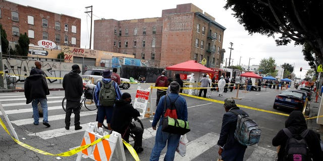 FILE: People line up to take a COVID-19 test in the Skid Row district in Los Angeles.