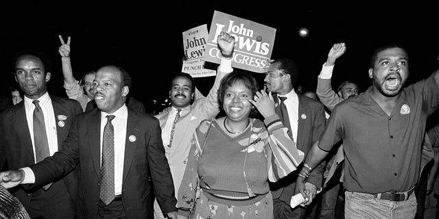 In this Tuesday night, Sept. 3, 1986, file photo, John Lewis, front left, and his wife, Lillian, holding hands, lead a march of supporters from his campaign headquarters to an Atlanta hotel for a victory party after he defeated Julian Bond in a runoff election for Georgia's 5th Congressional District seat in Atlanta.