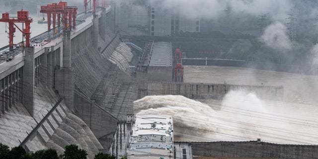 In this photo released by China's Xinhua News Agency, water flows out from sluiceways at the Three Gorges Dam on the Yangtze River near Yichang in central China's Hubei Province, Friday, July 17, 2020. Engorged with more heavy rains, China's mighty Yangtze River is cresting again, bringing fears of further destruction as seasonal floods that already have left more than a hundred people dead or missing have grown in force since last month. (Zheng Jiayu/Xinhua via AP)
