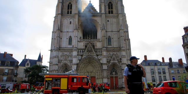 Fire fighters brigade work to extinguish the blaze at the Gothic St. Peter and St. Paul Cathedral, in Nantes, western France, Saturday, July 18, 2020. (AP Photo/Laetitia Notarianni)