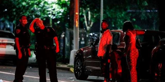 Police officers speak to locals at a crime scene on Atlantic Avenue where two individuals were injured by gunfire on July 18 in Brooklyn. Police statistics show more people have been shooting victims this year than all of last year. (AP Photo/John Minchillo)