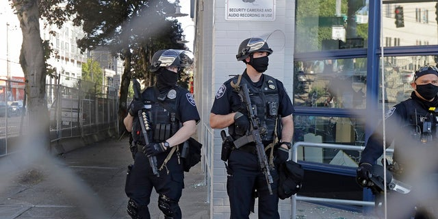 Seattle police officers hold weapons as they stand guard outside the East Precinct Building recently. (Associated Press)