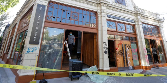 A worker clears glass from broken windows at the Starbucks Roastery, Sunday, July 19, 2020 in Seattle's Capitol Hill neighborhood. Protesters broke windows at the store earlier in the afternoon. (AP Photo/Ted S. Warren)