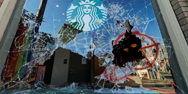 Broken windows are shown at a Starbucks store, Sunday, July 19, 2020 in Seattle's Capitol Hill neighborhood. Protesters broke windows at the store earlier in the afternoon. (AP Photo/Ted S. Warren)